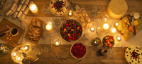Overhead view candlelight table with Christmas desserts