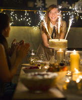 Enthusiastic woman serving cake with sparkler fireworks to clapping friends 11086027161| 写真素材・ストックフォト・画像・イラスト素材|アマナイメージズ