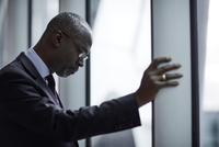 Serious businessman looking down at window 11086027197  写真素材・ストックフォト・画像・イラスト素材 アマナイメージズ
