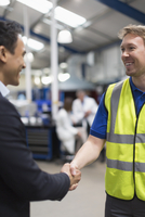 Smiling manager and worker handshaking in steel factory
