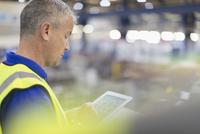 Supervisor using digital tablet in steel factory