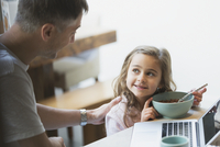 Father and daughter eating breakfast at laptop