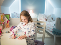 Girl in pajamas coloring at desk in bedroom