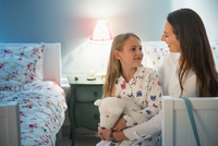 Mother and daughter talking at bedtime in bedroom