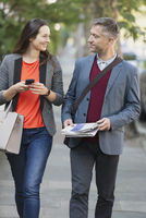 Business couple walking and talking on sidewalk