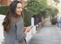 Portrait smiling businesswoman with cell phone looking back on sidewalk