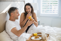 Smiling couple enjoying breakfast in bed