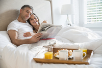 Smiling couple reading newspaper enjoying breakfast in bed