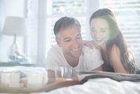 Smiling couple reading newspaper in sunny bedroom 11086027610| 写真素材・ストックフォト・画像・イラスト素材|アマナイメージズ