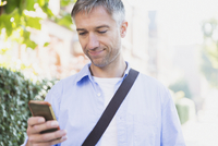 Businessman texting with cell phone outdoors