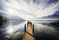 Couple at the edge of dock over sunny tranquil lake, Switzerland