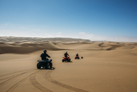 Friends riding quadbikes in sunny desert, Swakopmund, Namibia