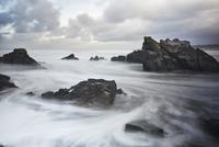 Long exposure ocean swirling around rocks, Devon, United Kingdom