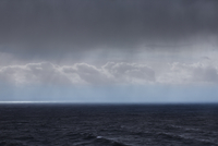 Clouds and rain over ocean seascape
