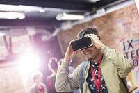 Man trying virtual reality simulator glasses at technology conference 11086027806| 写真素材・ストックフォト・画像・イラスト素材|アマナイメージズ