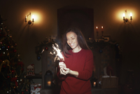 Smiling woman with sparkler firework in dark living room with Christmas tree