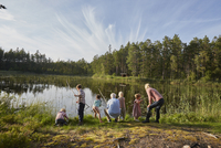 Grandparents and grandchildren fishing at sunny lakeside in woods