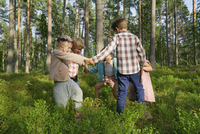 Boys and girls holding hands in circle among trees in woods