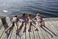 Boys and girls laying on dock looking down at lake 11086027898| 写真素材・ストックフォト・画像・イラスト素材|アマナイメージズ