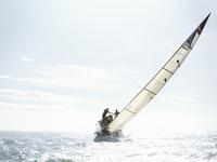 Sailboat tilting on sunny ocean 11086027916| 写真素材・ストックフォト・画像・イラスト素材|アマナイメージズ