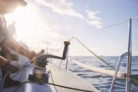 Man adjusting sailing winch on sailboat