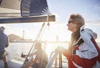 Woman sailing steering sailboat at helm on sunny ocean 11086027964| 写真素材・ストックフォト・画像・イラスト素材|アマナイメージズ