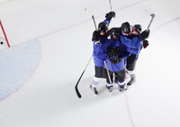 Hockey team in blue uniforms cheering celebrating on ice
