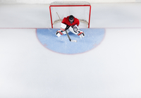 Hockey goalie in red uniform protecting goal net