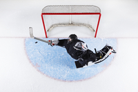 Overhead view hockey goalie reaching to block puck at goal net