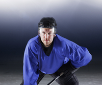 Portrait determined hockey player in blue uniform on ice