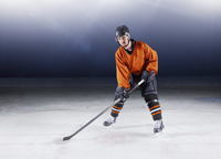 Portrait confident hockey player in orange uniform on ice