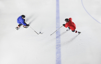 Overhead view hockey players going for puck on ice