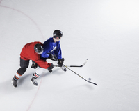 Hockey players going for puck on ice