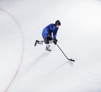 Hockey player in blue uniform skating with puck on ice