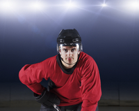Portrait confident hockey player in red uniform