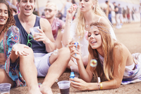 Young friends hanging out blowing bubbles at music festival