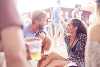 Young couple drinking beer and talking at music festival 11086028085| 写真素材・ストックフォト・画像・イラスト素材|アマナイメージズ