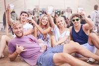 Portrait young friends with beer hanging out at music festival 11086028093| 写真素材・ストックフォト・画像・イラスト素材|アマナイメージズ