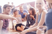 Young friends hanging out drinking beer and talking at music festival 11086028094| 写真素材・ストックフォト・画像・イラスト素材|アマナイメージズ