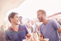 Young men drinking and laughing at music festival