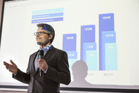 Businessman with microphone speaking at projection screen with bar chart
