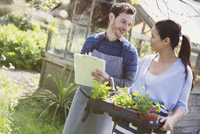Plant nursery owners with clipboard and potted plants 11086028852| 写真素材・ストックフォト・画像・イラスト素材|アマナイメージズ