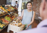 Woman with basket smiling at grocery store worker 11086028853  写真素材・ストックフォト・画像・イラスト素材 アマナイメージズ