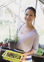 Portrait smiling woman gardening in greenhouse