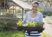 Portrait smiling woman carrying potted plants outside greenhouse garden 11086028913| 写真素材・ストックフォト・画像・イラスト素材|アマナイメージズ