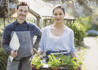 Portrait confident plant nursery workers with clipboard and potted plants outside greenhouse