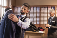 Tailor adjusting suit on dressmakers model in menswear shop 11086029129| 写真素材・ストックフォト・画像・イラスト素材|アマナイメージズ