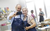 Senior couple taking selfie in pottery studio