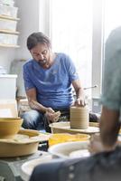 Mature man using pottery wheel in studio