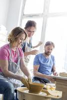 Teacher guiding mature couple using pottery wheel in studio